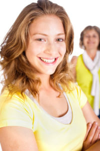 Gorgeous woman in focus with her mom in the background isolated on white